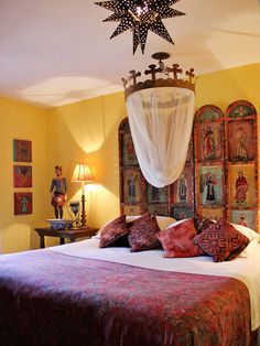 New Mexican / Mexican style decor - Santos and retablos with set from a yellow wall. Tinwork lighting.