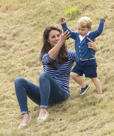 The playful prince: George stomps down the hill clutching two handfuls of grass while his mother Kate helps him keep his balance June 14/15