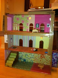 Doll house with kleenex box elevator, stairs, balcony, doors and windows made from cardboard boxes, scrapbook paper, glue, tape and battery powered tea lights.