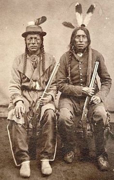 this is an interesting picture of what would be late 1800's Native Americans. You can see the influences of settlers in the hat, jacket, and rifles while still retaining other elements of their culture.