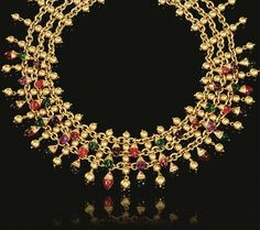 GEM-SET AND YELLOW GOLD NECKLACE, 'NATURALIA', BULGARI, 1990S Designed as a wide band of three gold chains set at intervals with gold beads, the front supporting a graduated fringe of stylised fish, their heads pavé-set with brilliant-cut diamonds, their bodies carved in amethyst, peridot and pink tourmaline, signed Bulgari, case by Bulgari.
