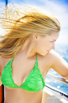 Beautiful young blonde female tourist with her hair blowing in the ocean breeze looking out over the sea on a travel cruise by Ryan Jorgensen
