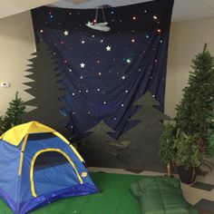 Dark blue sheet, Christmas lights, tent, sleeping bag, and silhouettes of trees.