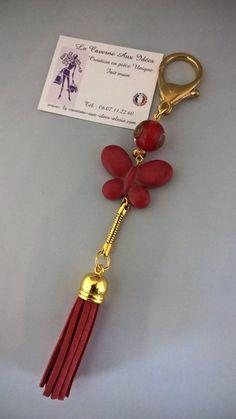 bijou de sac pompon rouge et papillon
