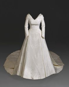 The dress was developed layer by layer, from the corset and complex underskirt to the fitted bodice and full pleated skirt. The dress has a neckline that folds around the shoulders to a low back, which drapes into a flowing full-length train. Royal Wedding Gowns, Royal Weddings, Wedding Dresses, Wedding Outfits, Kids Bridesmaid Dress, Eugenie Wedding, Burgundy Wedding Cake, Kate Middleton Wedding, Princess Eugenie