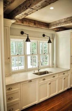 Kitchen with white cabinets, gray marble countertops, wooden beams, hardwood floors. I love this!! by Colleen Love