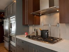 The vertical backsplash tile behind the range is mixed with stainless steel inserts to accent the stainless steel appliances and cabinet pulls.