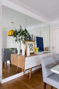 Apartamento moderno, decoração com parede de espelhos, aparador de madeira e cadeiras cinza.