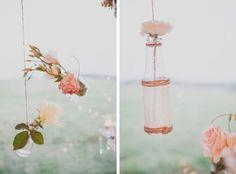 Roses suspended in simple glass bottles via The Lane