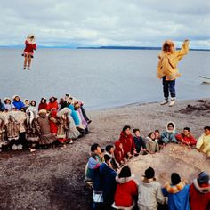NATIVE ALASKANS PLAYING A GAME OF NULUKATUK, IN WHICH INDIVIDALS ARE TOSSED INTO THE AIR