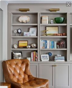 Cognac Leather Tufted Corner Reading Chair Is Positioned On Caster Legs In Front Of Built Styled Gray Bookshelves Located Above Shaker TV Cabinets
