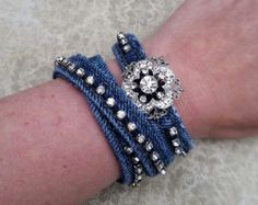 Denim wrap bracelet, upcycled jeans, denim jewelry, recycled jeans Denim is very popular right now. This upcycled, denim wrap bracelet is the perfect finishing touch to an outfit. It was created with the seam of a pair of blue jeans. A rhinestone chain was carefully hand sewn to the bracelet. The stitches were sewn in a way that they are not seen on the backside of the bracelet. It is fastened with a silver toggle closure. The bracelet is 1/2 wide and is 15 long. The denim is a dark blue…