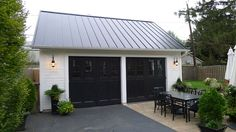 The black standing-seam-metal roof contrasts with the fresh white siding setting the garage apart from the main house. Metal Garage Doors, Metal Garages, Garage Door Design, Porsche Garage, Car Garage, Garage Roof, Garage Exterior, Exterior Homes, Exterior Paint