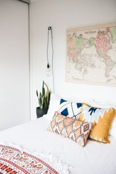 Simple white bedspread, patterned cushions + throw, plant and raw reading light... 26 Simple and Chic Master Bedroom Decorating Ideas | StyleCaster