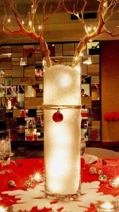 """Reindeer centerpiece: minimalism meets rustic w/Manzanita branch antlers, tall cylindrical vase, artificial snow and LED lights. Use a red ornament or jingle bell for the nose. Put a 4x12"""" vase inside 6x12""""vase; fill space in between w/snow. Firmly push branches into floral form in bottom of interior vase."""