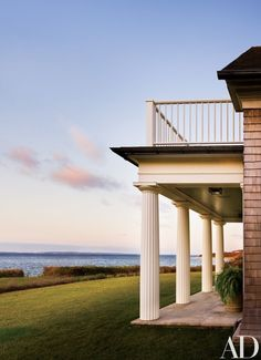 A view of Vineyard Sound from a terrace off the library; Doric columns—a nod to the island's beloved Greek Revival style—support a balcony off the master bedroom   archdigest.com