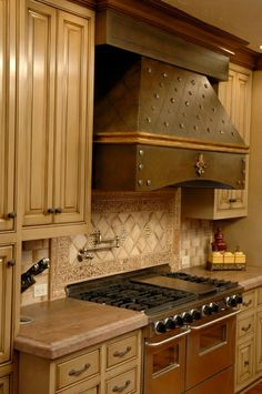 Modern Masters Metal Effects Rust Patina Finish on range hood with gold leaf and rivets | Project by Brush & Trowel.