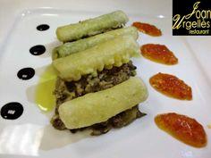 Calçots en tempura sobre un llit de trinxat de col amb botifarró, ceps i pernil ibèric, melmelada de tomàquet i caramel de Mòdena