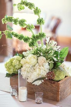 A barn wood box filled with white and green hydrangeas, white veronica, bells of Ireland, white roses, white agapanthus, and greenery.  Photograph by Half Orange Photography.