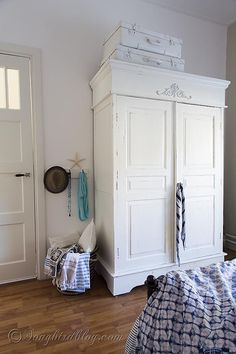 Bedroom decor. Ikea Hemnes mirror in bedroom with painted suitcases, white painted wardrobe and a pretty board with hooks via songbirdblog.c...