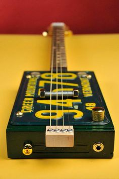"""Green Mountains 4-string license plate resonator. Padron 3000 cigar box. 1948 Vermont plate. Maple neck with walnut peg head; walnut fret board wit maple dots. Gold fret wire; gold closed-gear tuners; bone nut. Piezo disc attached to neck under bridge. 24.5"""" fret scale"""