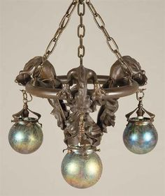 One of a pair of Art Nouveau Style Bronze and Art Glass Three-Light Fixture, the ring-shaped mount with three gargoyles with a central horn from which are suspended three Loetz style globe shades in colorless glass decorated with blue and green oil spot motifs and gold pulled feather motifs.