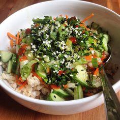 Brown rice bowl with cucumber, carrot, avocado, scallion, cilantro, basil, sesame, and a sauce made of sea salt, sesame oil, evoo, maple, lime juice, sriracha.