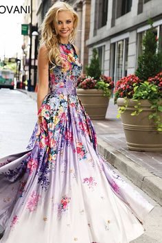 Multi color print sleeveless prom dress features round low back available in plus sizes.