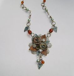 """""""Rusty Rose"""" by Novegatti Designs .... polymer clay roses with Swellegant coating and patina join aqua copper and rusty leaves on a whitewashed filigree for a time-worn casual look. Glass beads and rhinestones add a touch of sparkle. For more information and more goodies, see www.facebook.com/..."""