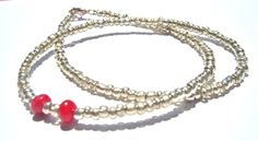 Silver Seed Bead Necklace with Red Coral detail Silver coloured seed beads have been threaded onto tiger tail wire. At the side of the necklace I have added two pieces of red coral to add contrast and create a beautiful necklace which can be worn any time day or night!