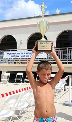 Marco DeCrescenzo, 7, of Cedar Knolls is named the King of Plop, holding the trophy, for his plop off a boogie board.  #OceanCity #OCNJ #kingofplop