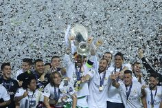 Real Madrid's Spanish defender Sergio Ramos (C) lifts the trophy as Real Madrid players celebrate winning the UEFA Champions League final football match over Atletico Madrid at San Siro Stadium in Milan, on May 28, 2016. / AFP / OLIVIER MORIN