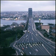 Sydney Harbour Bridge at dusk  This photograph from the David Mist archive shows the Sydney Harbour Bridge from a unique perspective. The bold composition with the central placement of the Bridge obscuring its very familiar coat hanger shape leads the eye straight up and gives a sense of a path leading out of the city. Photographed in the 1970s, the traffic heading north at dusk seems sparse by today's standards.  Photography by Studio Ten    © All rights reserved
