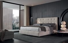 Arca bed with quilted headboard, 01 latte Nabuk leather removable covering. Bed-set in 06 roccia and 08 polvere Provence with white piping stitching style. You night table in spessart oak. Tribeca with piombo painted metal structure and Calacatta oro marble top.