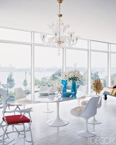 A Saarinen-style dining table takes a starring role in a modern New York City dining room. The space merges midcentury pieces with an opulent glass chandelier and a whimsical antler chair.