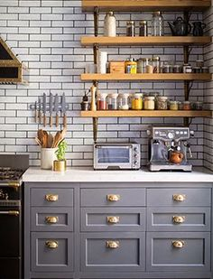 slate grey cabinetry with brass hardware and rustic open shelving