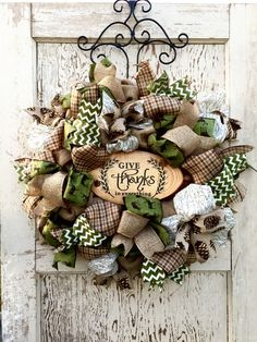 """This rustic fall wreath has a log center that states """"Give Thanks"""". It has deer themed, pine cones, plaids, wood, and chevron printed ribbons. The wreath is built on a burlap base and measure approxim"""
