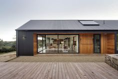 Lookout House - Warm wood and grey siding open to outdoor patio