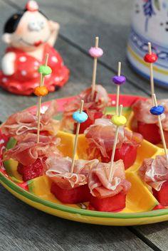 Sangria meloen met Serranoham   Ingrediënten: • watermeloen • 1 fles Sangria • plakjes Serranoham. Snijd de watermeloen in blokjes. Doe ze in een goed afsluitbare jampot (weckpot of een vacuümzak), overgiet het met een fles Sangria tot het fruit onder staat. Bewaar het tot gebruik in de koelkast. Verwijder de blokjes meloen uit de Sangria.  Halveer een plakje Serranoham en prik met een klein vorkje of prikker de ham op een blokje meloen. In plaats van ham kun je ook kaas gebruiken. #hapje