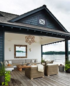 Outdoor Patio on the Lake with beadboard wall, geometric chandelier, chevron banquet pillows, planters with potato vine and wicker armchairs - Anne Hepfer