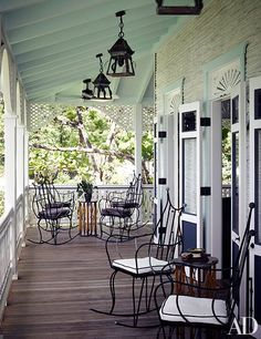 A porch floored with ipe planks wraps around the clubhouse; the building's whitewashed siding is reclaimed palm wood | archdigest.com