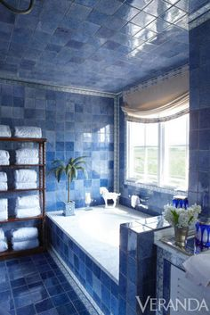 Bold blue tiles are layered floor-to-ceiling throughout this bathroom, lending the space a jewel-box feel. The white marble tub offers a break from the color without detracting from its impact.