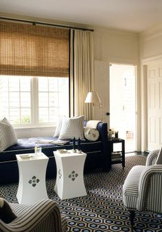 A toned down blue and beige color palette works perfectly with the pattern play on the bold rug, chairs and daybed.