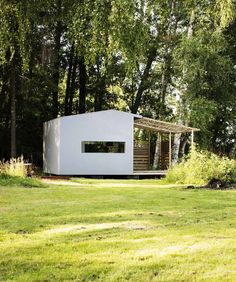Tiny prefab cabin with white exterior and wooden deck