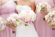 Pinkish-purple bridesmaid dresses with the bride in, obviously, white.