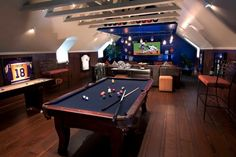 """Here we a have a lovely contemporary roof space conversion into and combined games room and theatre man cave. Created by J. Hettinger Interiors the dark wood gives the whole space a very grown-up feel and the blue accents via the painted areas, display cases and pool table felt create a unifying theme. """