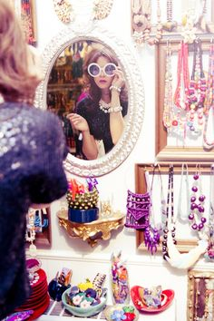 Dressing room inspiration. Framed mirror surrounded by like blank frames containing jewelry and possibly cosmetics.