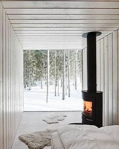 Finnish cabin bedroom with glass wall and stove