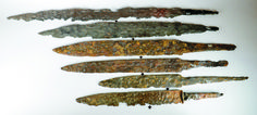 Six Frankish seaxes from Mainz, Germany, 6th to 8th century (edge is downwards, the arrow indicates the line of balance), from top 909.15.11 (8th century, 68.9 cm long, 438.9g); 909.15.12 (58 cm long, 599.6g); 909.15.13 (57 cm long, 633.4g); 909.15.15 (50 cm long, 415.8g); 909.15.23 (45 cm long, 319.5g); 909.15.22 (6th century, 42.3 cm long, 348.9g) - photo by Kay Sunahara.