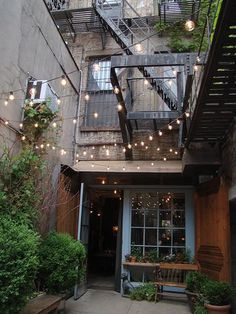 Outdoor space strung with lights. I can't believe someone has this space to enjoy!